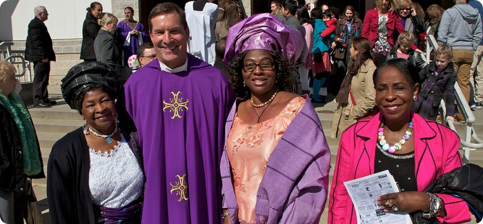 Priest smiling with three ladies next to him