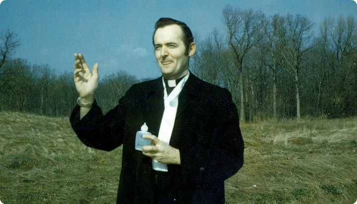 Father Hurley with Holy Water near a forest.